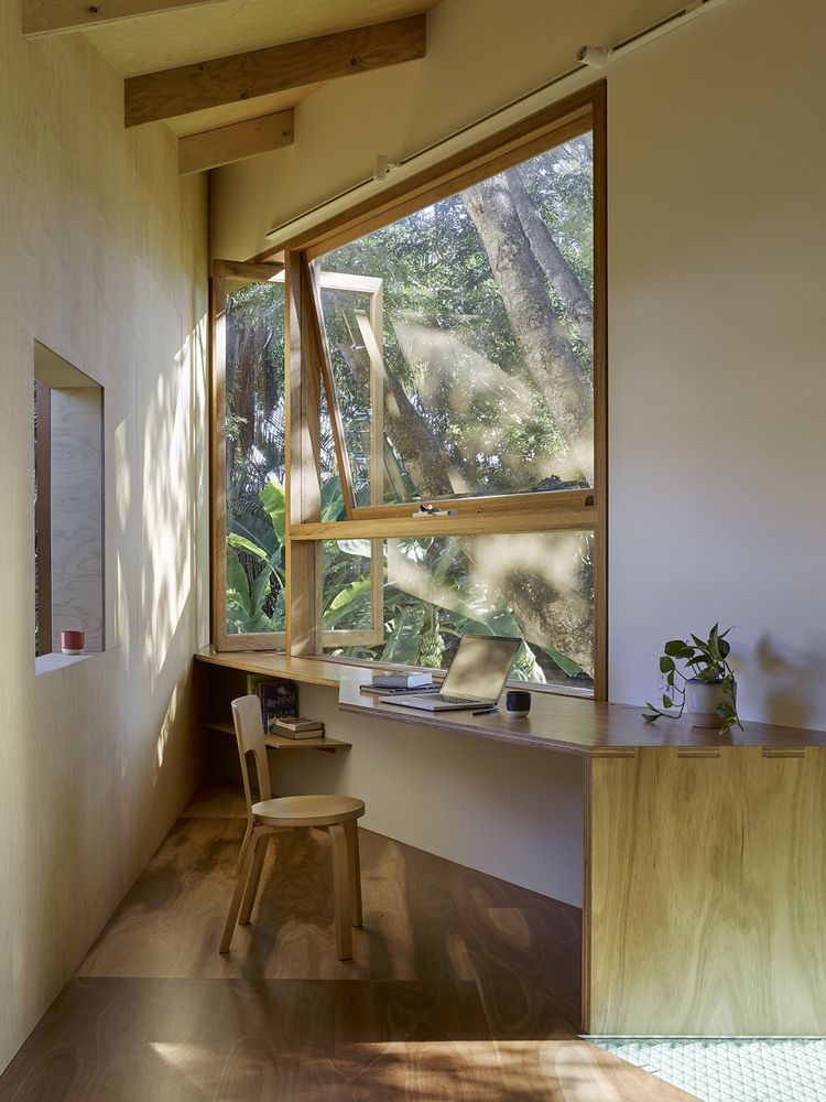 Upstairs, a custom-designed desk is positioned in front of the large window