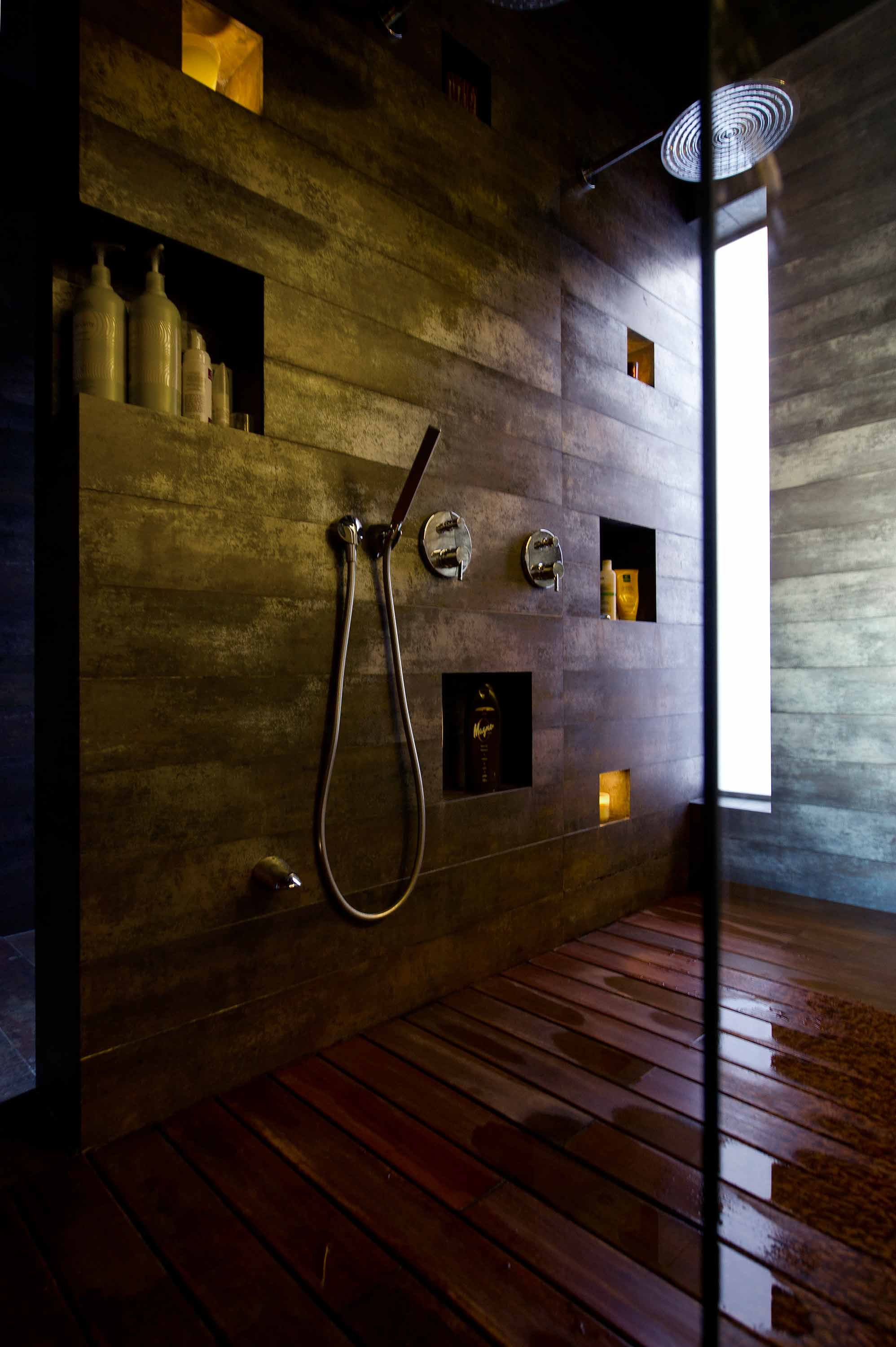 Inset spaces provide enough shelving for shower products and accessories like candles.