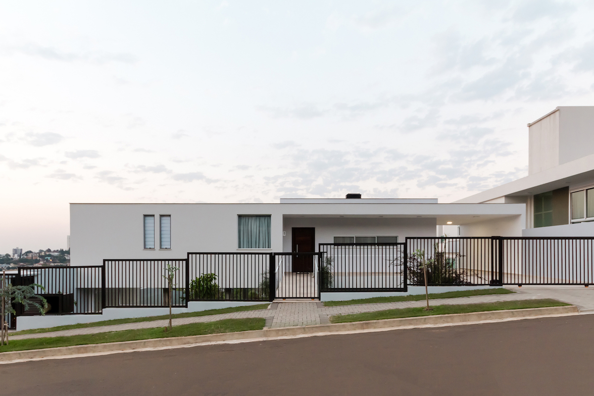 The house, white all around, sits on a sloped site with panoramic views of the city