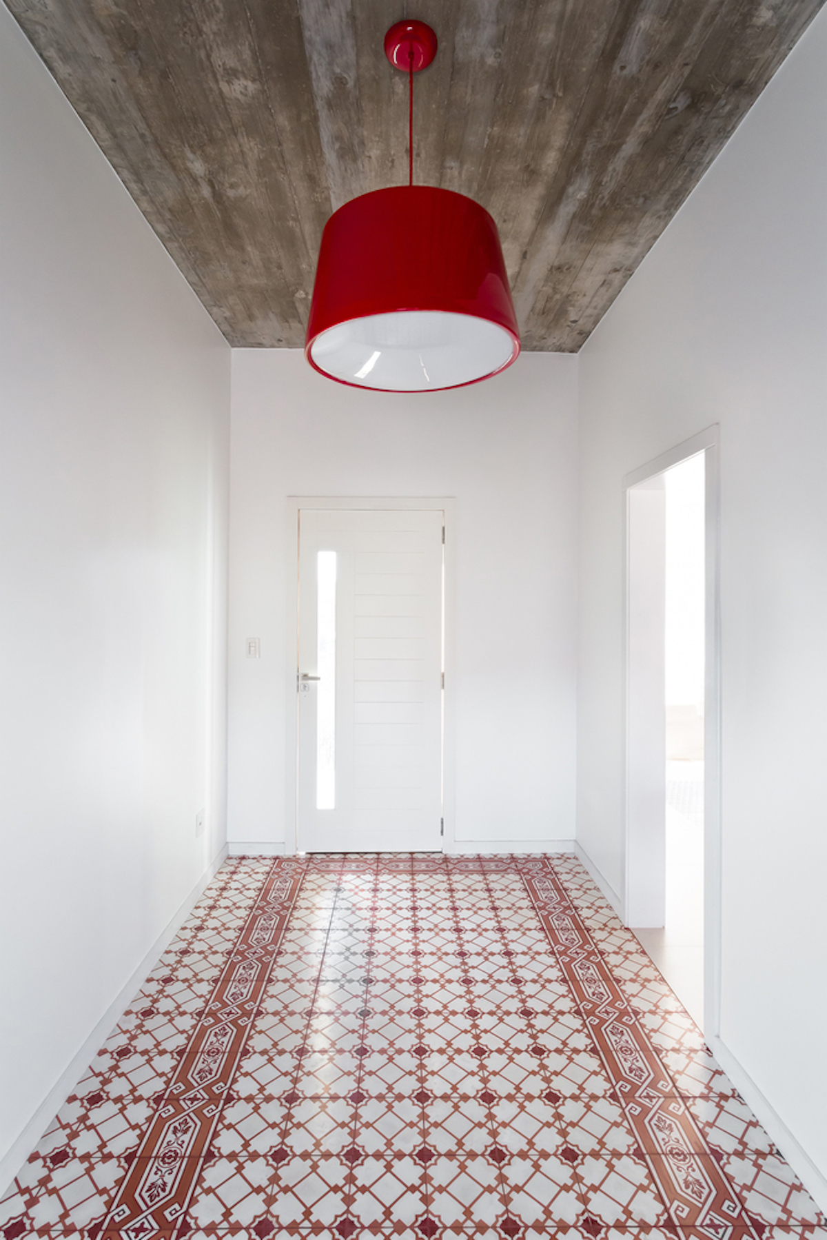 The entrance hallway is white with an exposed concrete ceiling and red accent details