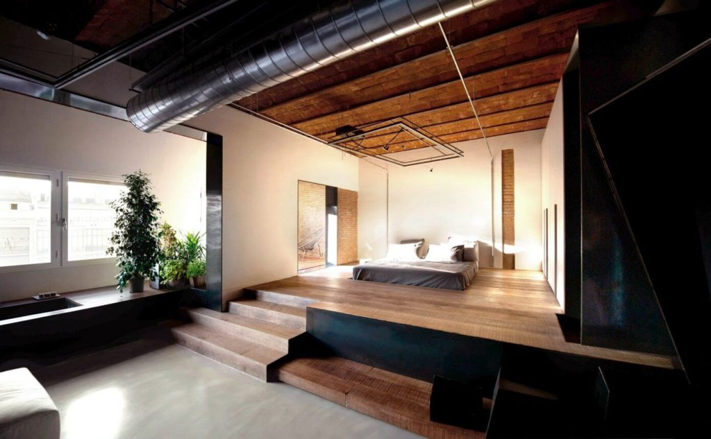 The bed is elevated on a platform, separating it from the bath area without dividing the space visually.