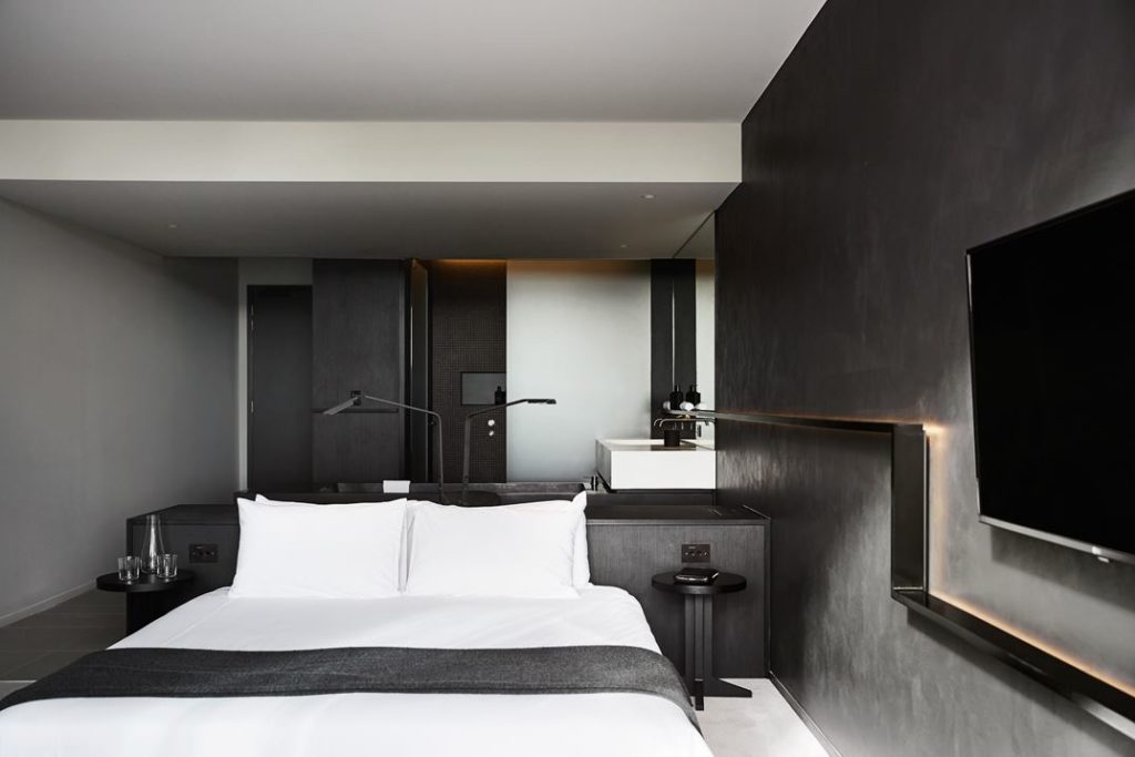 Modern lamps and a lighted shelf that runs the length of the wall are angular elements.