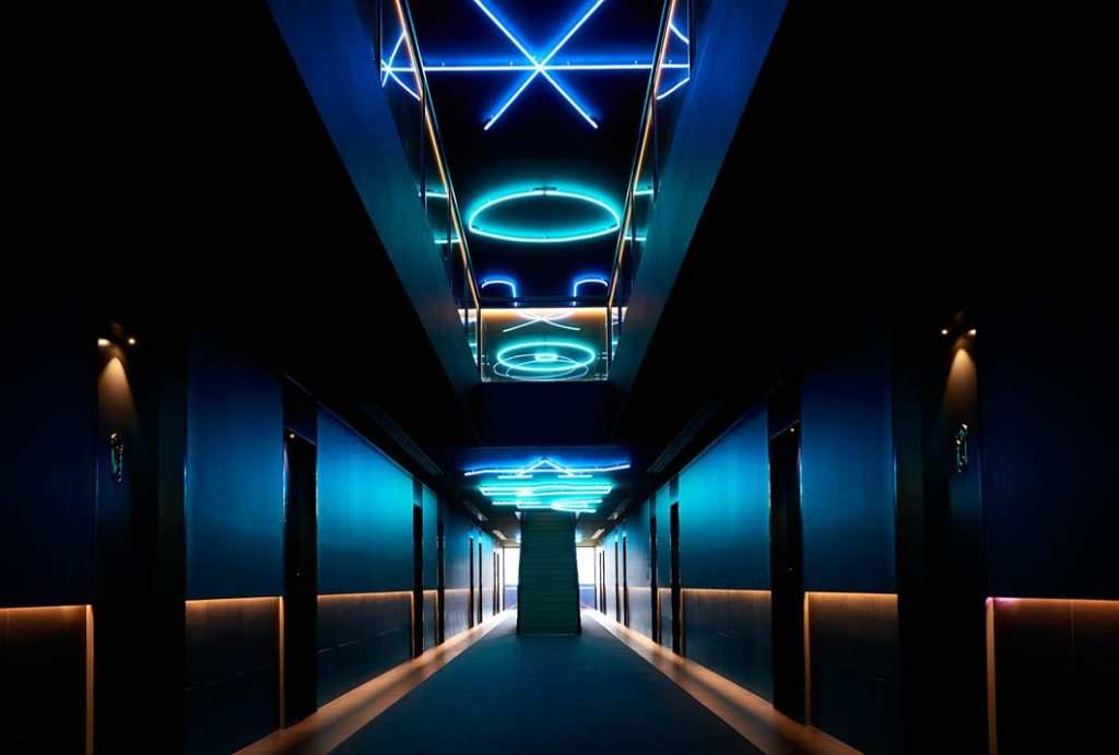 Low lighting is enhanced by the neon ceiling.