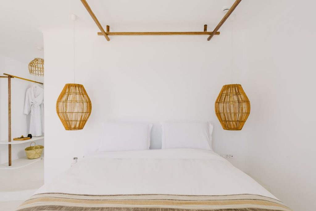 Clean white bedroom with pendant hanging lamps over the night stands