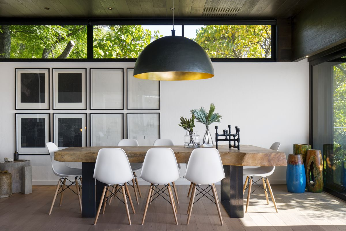 An oversized pendant lamp hangs above the dining table, complementing the otherwise simple setup