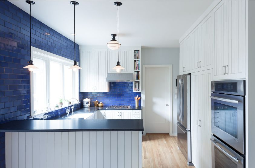 These blue subway tiles extend the kitchen backsplash all the way up to the ceiling and establish a beautiful focal point