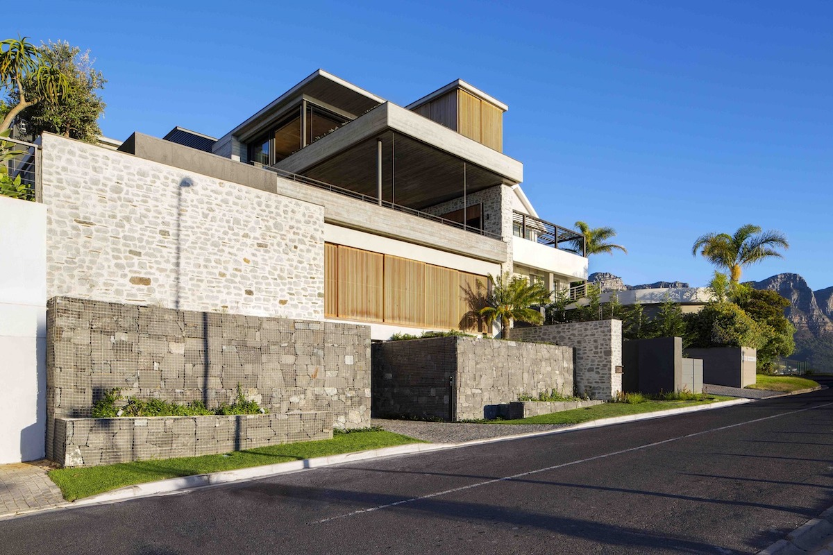 Gabion walls frame the house and the garage, establishing a buffer between the facade and the street