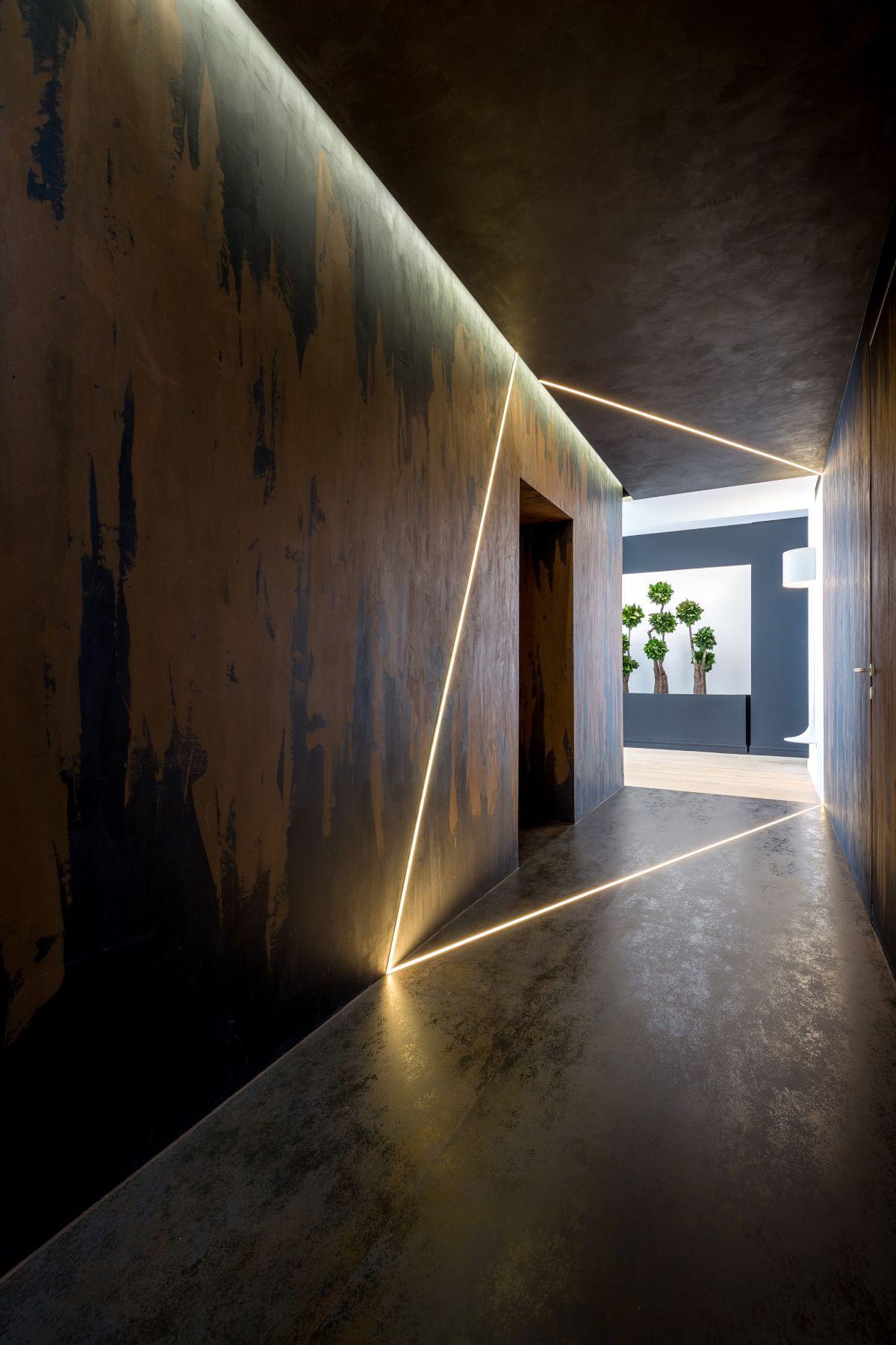 An unusual, dark entryway creates drama as people enter the apartment.