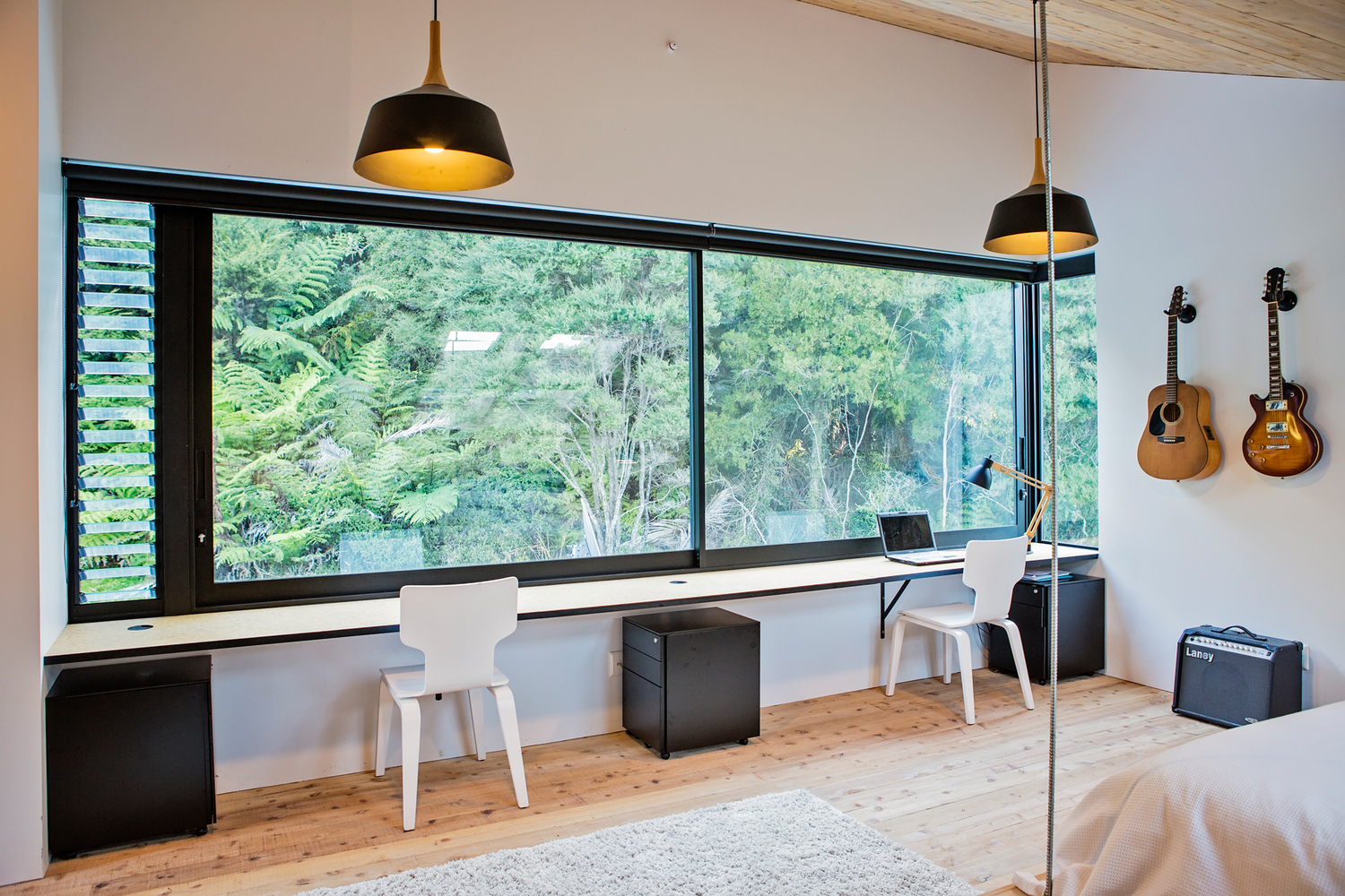 The master bedroom has a two-person desk placed in front of the windows