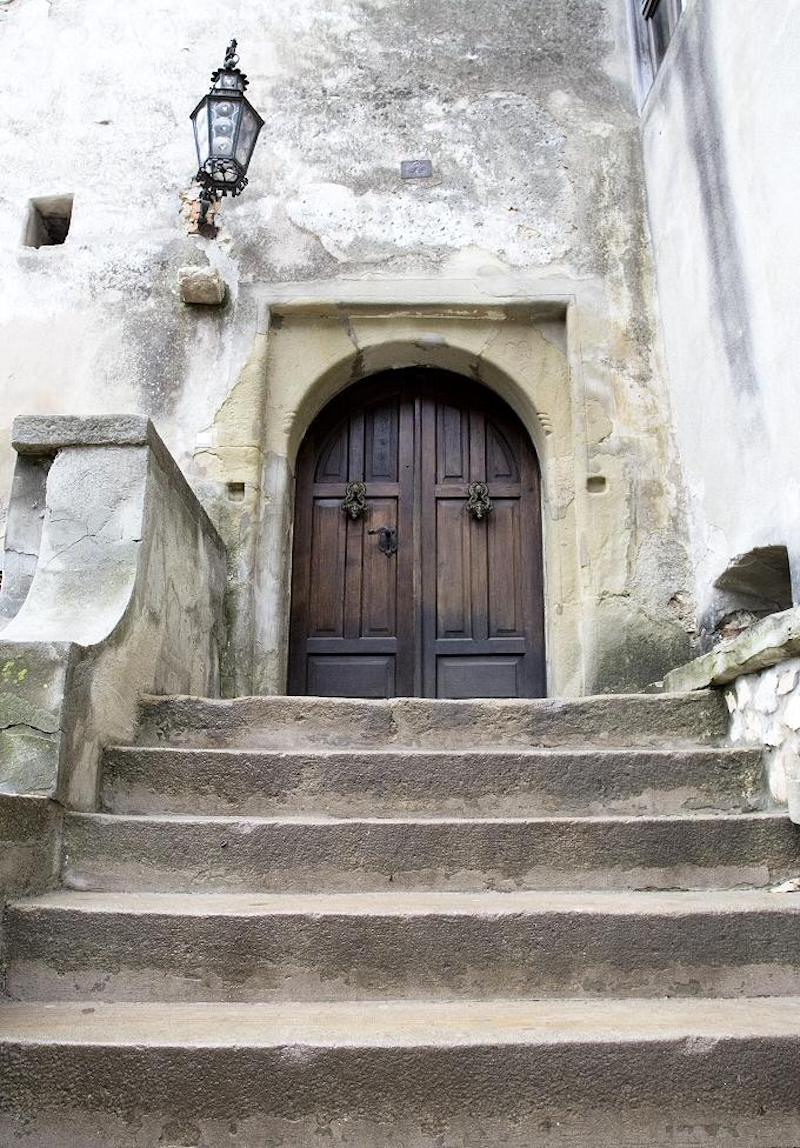 Visitors are welcomed inside the castle through a massive pair of wooden doors at the stop of a concrete staircase