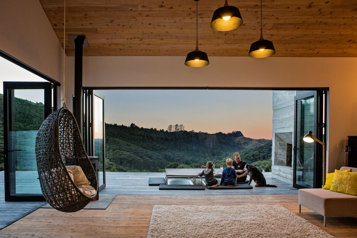 Glass doors open the living room entirely on two sides, letting in the views and fresh air