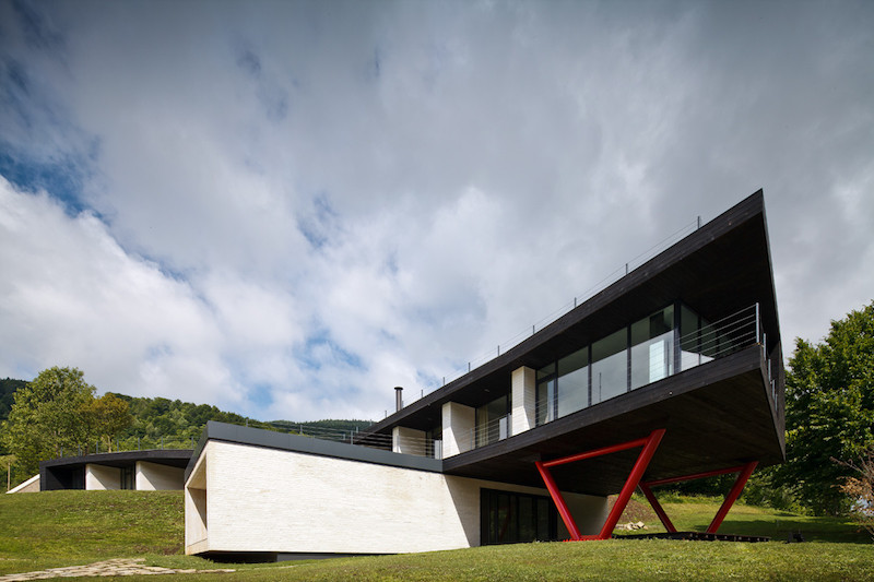 The hotel is organized into two main volumes, one of which is partially cantilevered, suspended on red poles