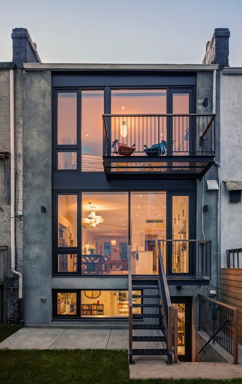 The back facade of the house has a two-storey glass wall and balconies that extend the spaces outdoors