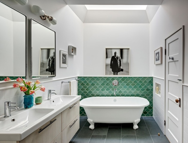 The main bathroom has a skylight above the tub and refreshing green tile accents