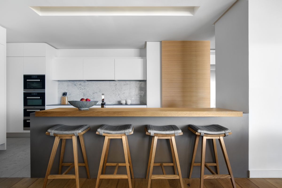 The bar stools are the visual link between the island's body and countertop as well as the wall panel at the back