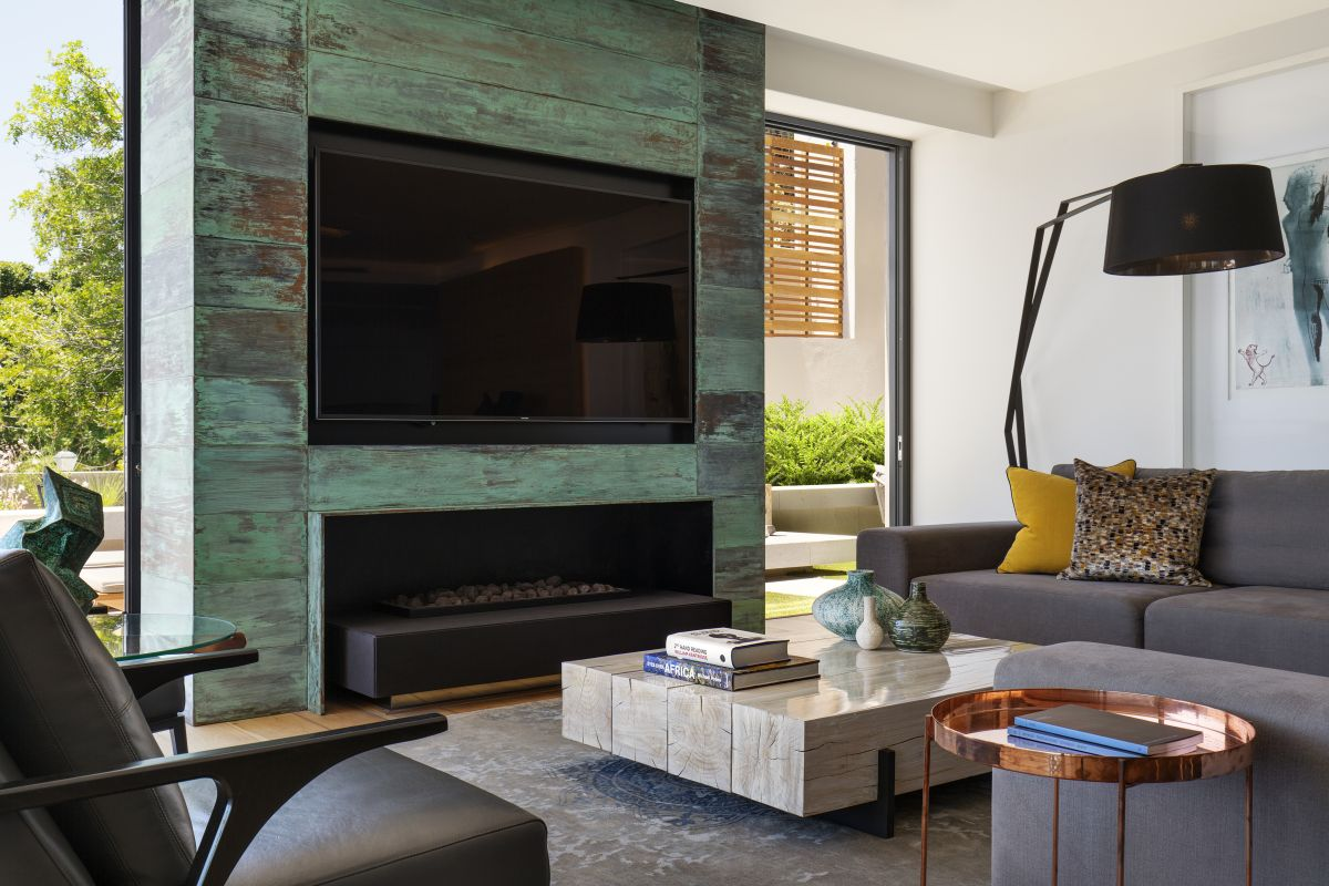 The TV is placed above a modern fireplace and together they fill the accent wall just right