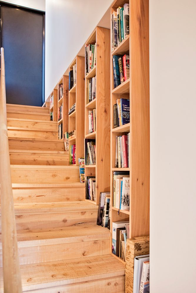 The staircase that links the two floors is made of wood as well and has a set of bookshelves on its side