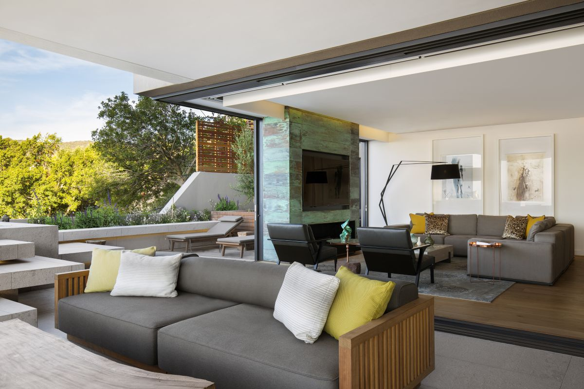 On the left side of the TV wall, the living space opens up to an outdoor terrace which serves as an extension of it