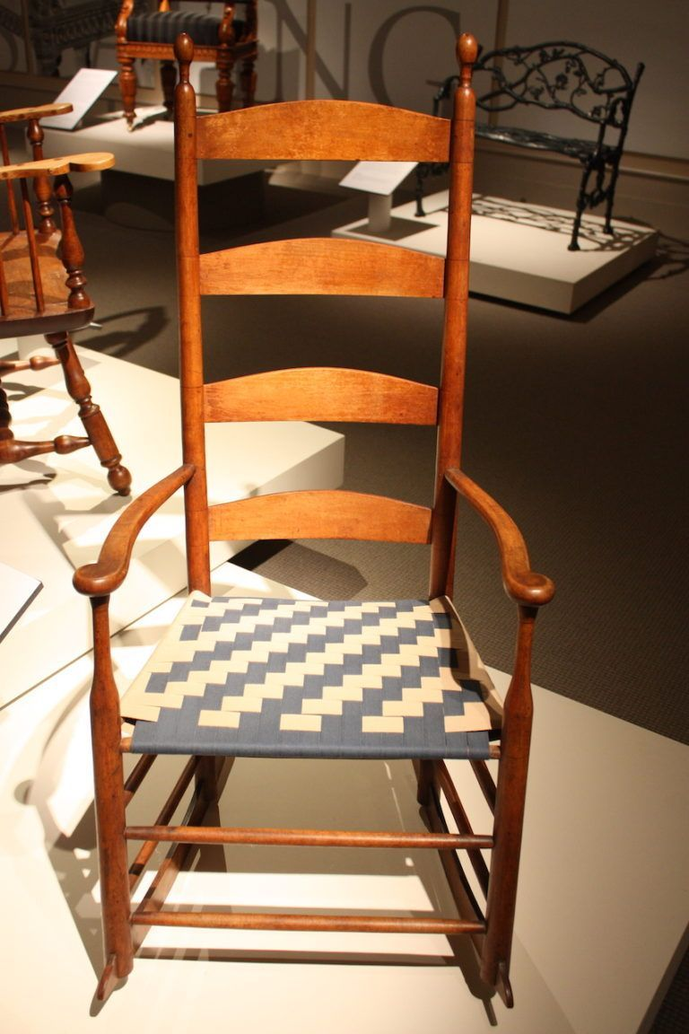 A traditional shaker style rocker is made of wood with a woven seat.