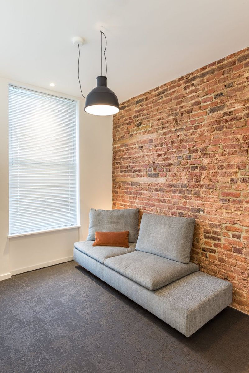 Exposed bricks add warmth, texture and color to the living space and contrast with the rest of the decor