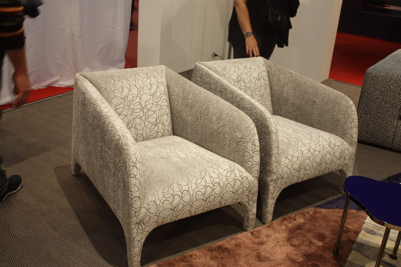 A more elegant take features upholstered legs and smoothly angled armrests.
