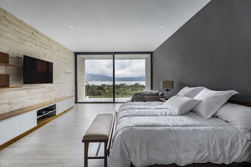 The bedroom frames its own stunning view of the lake and surrounding landscape