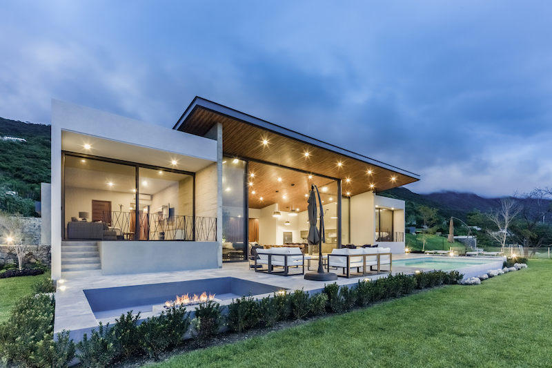 The wooden roof on the living area extends outside and cantilevers over the poolside deck