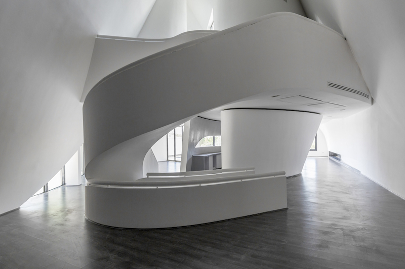 The staircase spirals around and undulates like a lightweight ribbon, linking the spaces seamlessly
