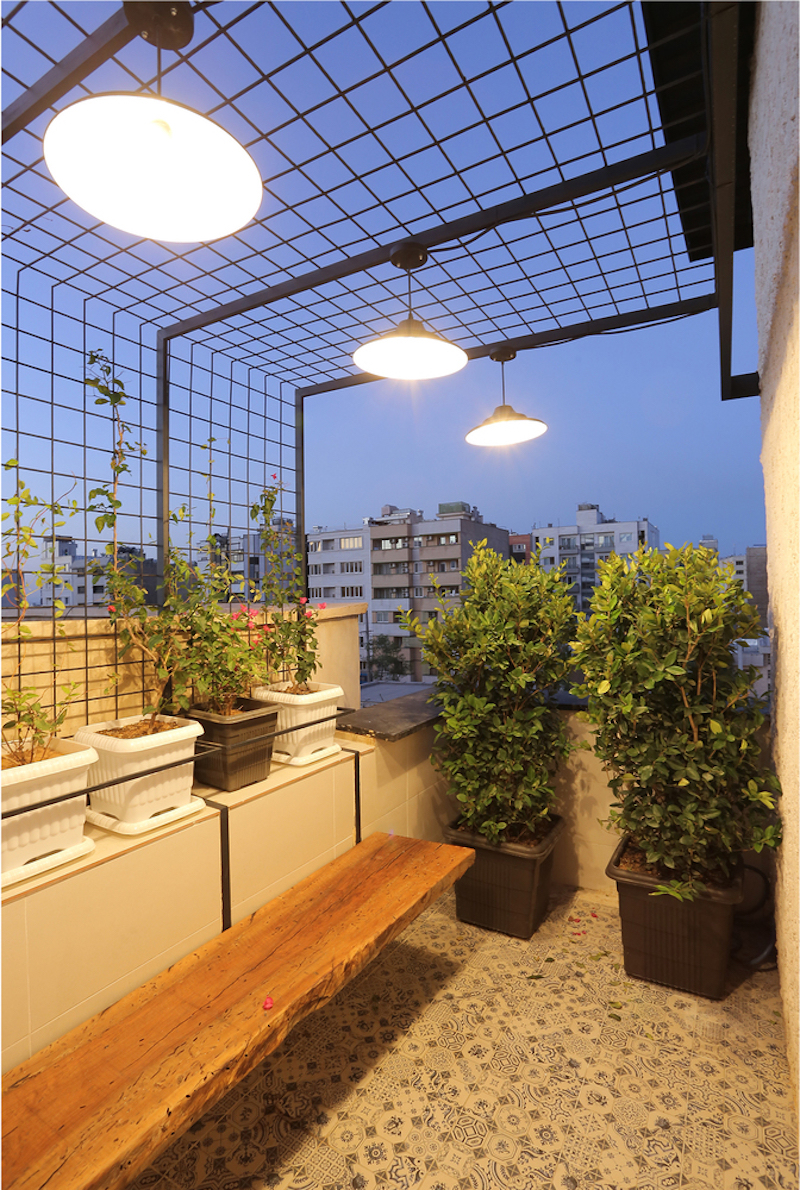 The terrace is framed by metal mesh and vines which control the light and privacy