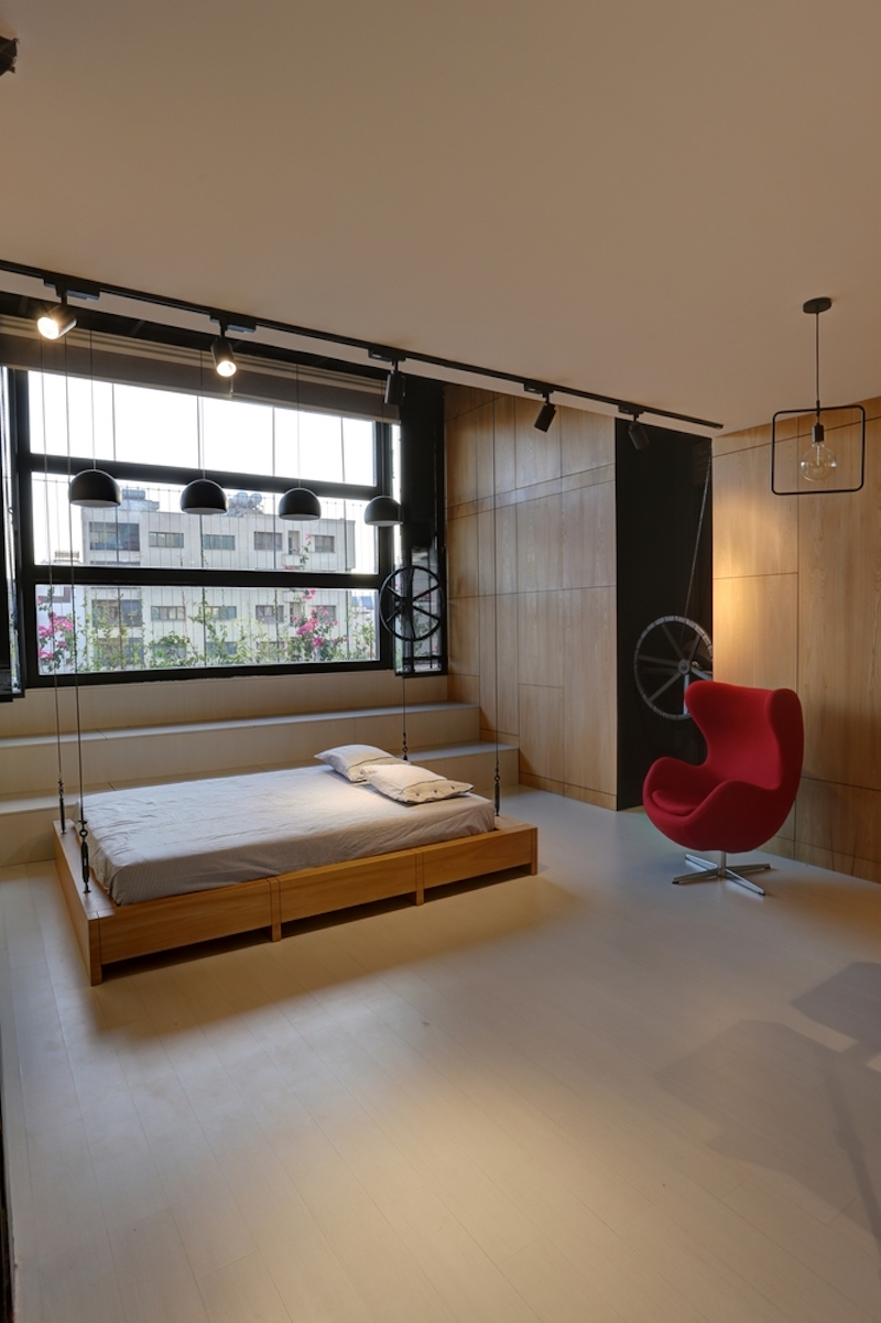 The bed is positioned close to the window and its frame is suspended from the ceiling