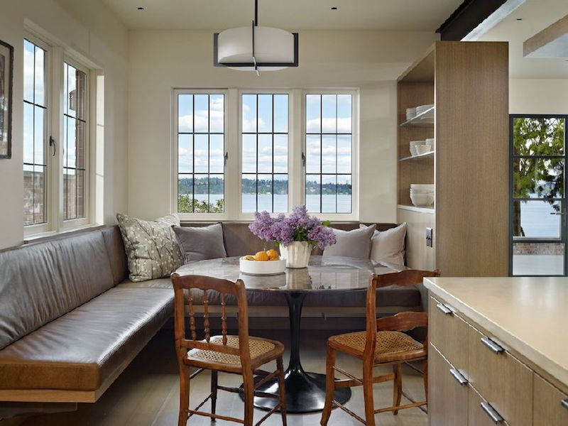 The kitchen has a cozy nook with a comfortable bench and a round pedestal table