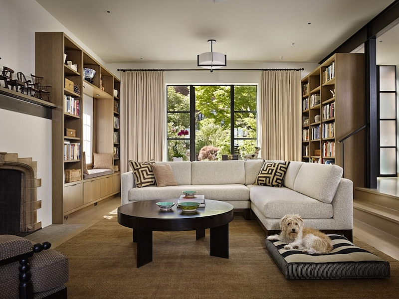 The living room has a fireplace and a sofa framed by bookshelves and garden views