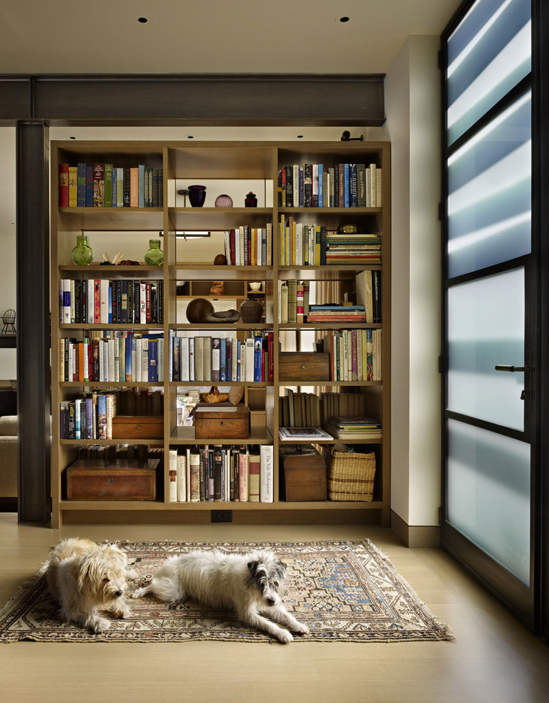 One of the bookcases doubles as a divider between the entryway and the living area