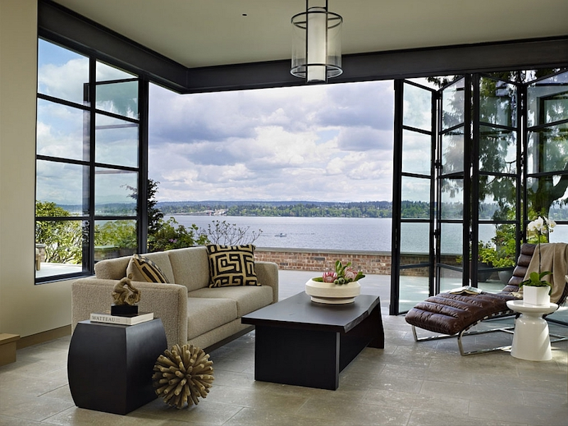 Large windows and folding glass doors reveal the beautiful views of the lake, bringing them inside the house