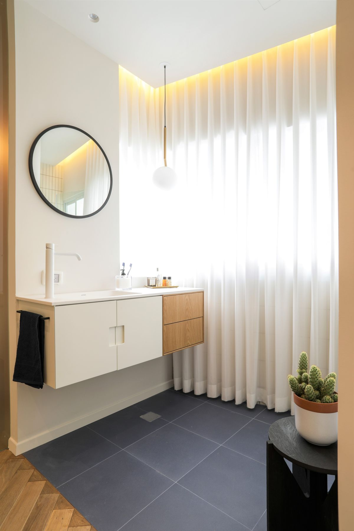 The lack of a permanent wall by the vanity makes the bathroom seem larger.