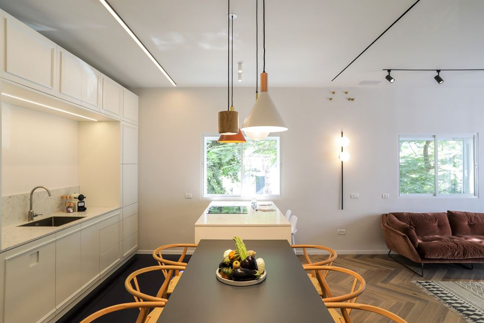 The darker table and dark, high-gloss floor accent the white kitchen cabinets.
