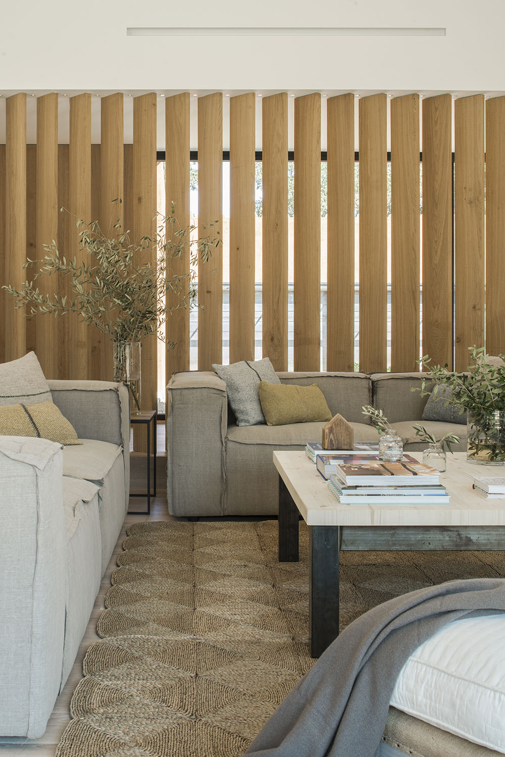 A slatted wall behind the sofa brings additional light into the space.
