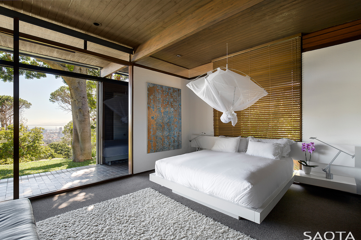 This breezy bedroom has an open and fresh decor and large windows that open it to the backyard