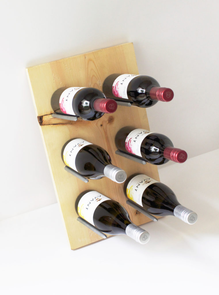 Wooden wine rack with large framing nails as supports