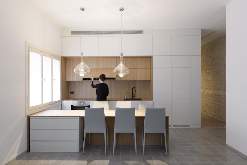The kitchen occupies a corner space and receives light through the windows and from the pendants
