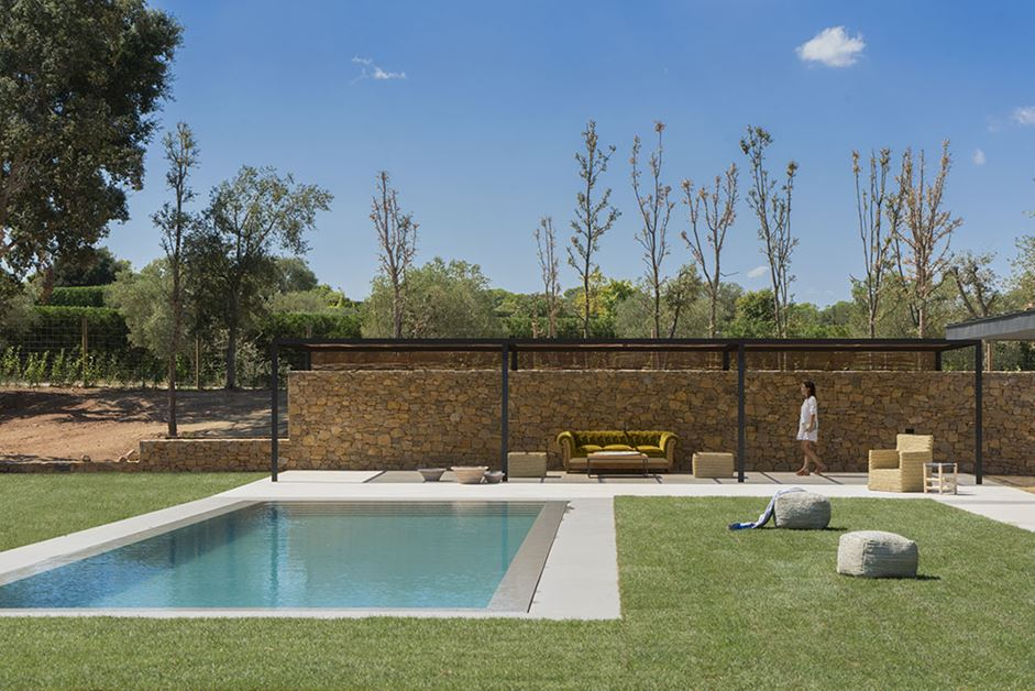 A stone wall provides privacy for the pool from the side and an overhang gives shade.