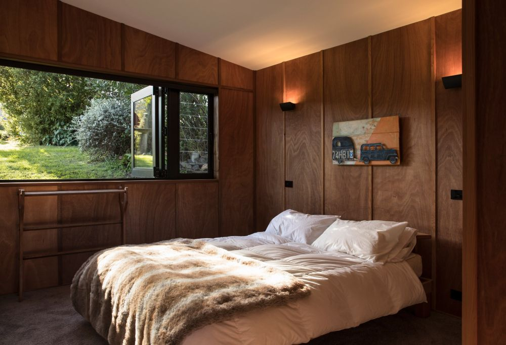 This cozy bedroom has walls lined in wood and a long and wide window with peaceful views