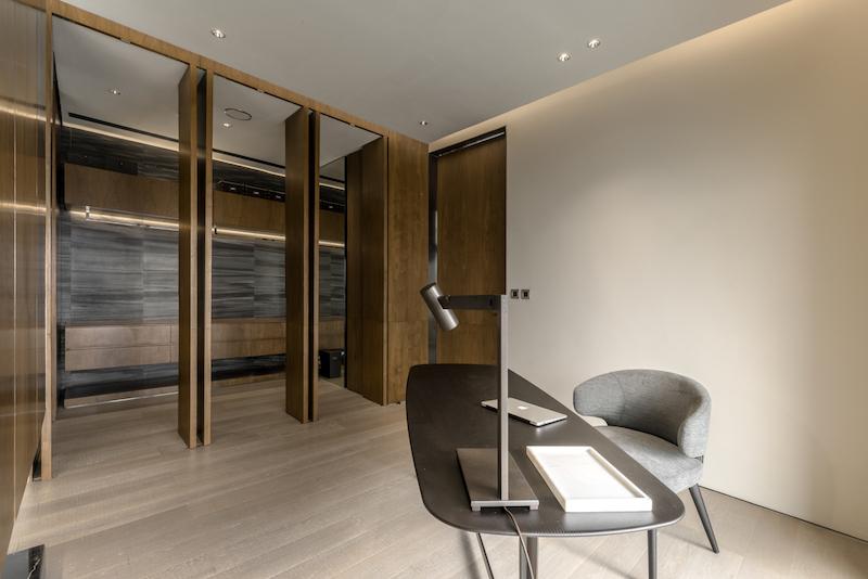 The en-suite bathroom is elegantly concealed behind wooden panels