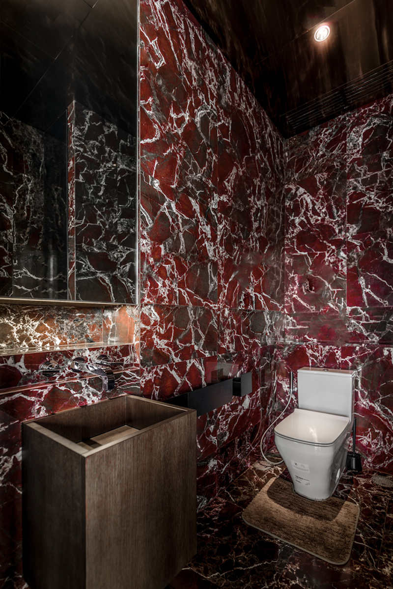 The smaller, second bathroom has a vibrant pattern on its walls and floor and an overall cool look