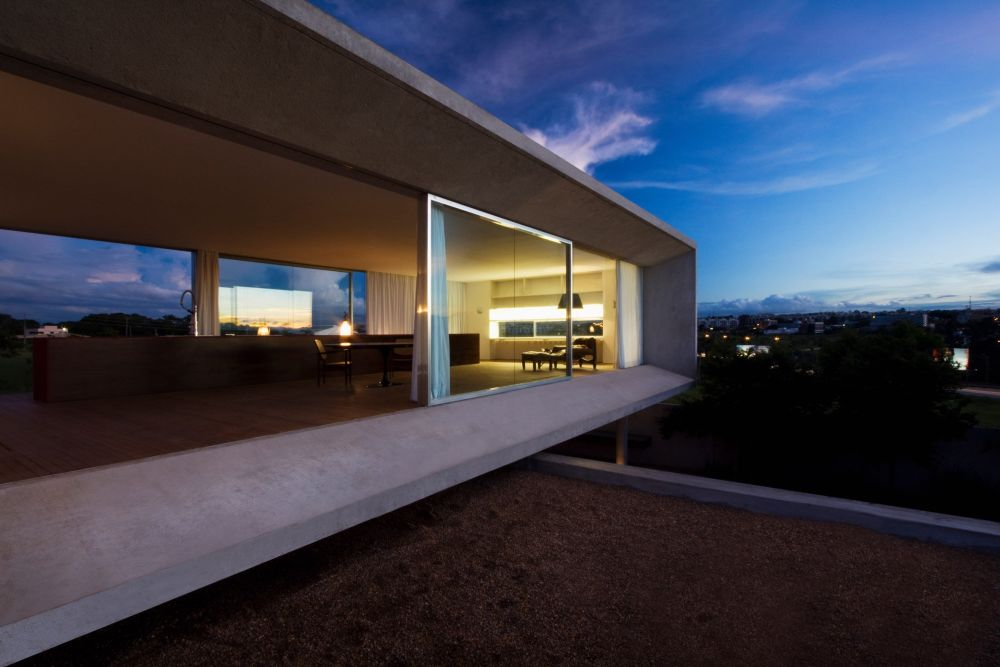The concrete shell of the top volume extends around it forming a sort of protective edge