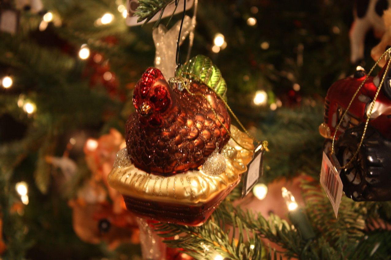 A glittery hen sits atop a basket in this whimsical little glass ornament.