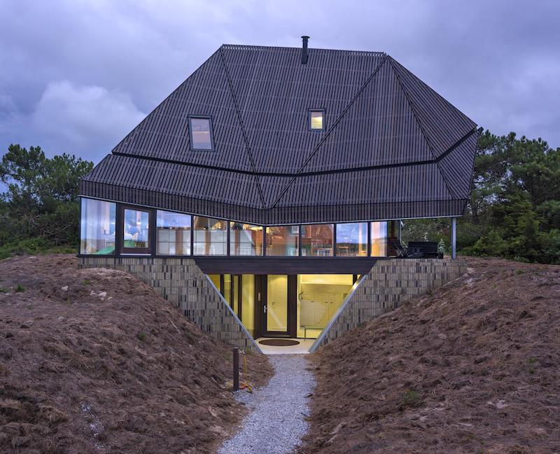 the faceted roof allows the house to visually coordinate with the forest behind it