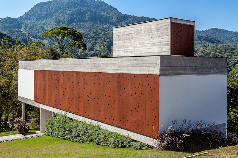 The western facade is partially covered in perforated panels made of corten steel