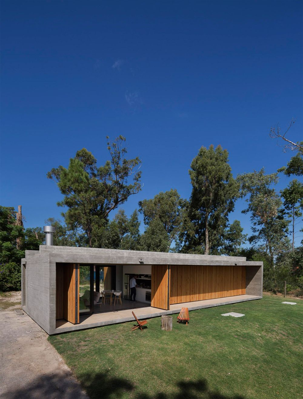 The house is long and rectangular and has a single level and a concrete shell
