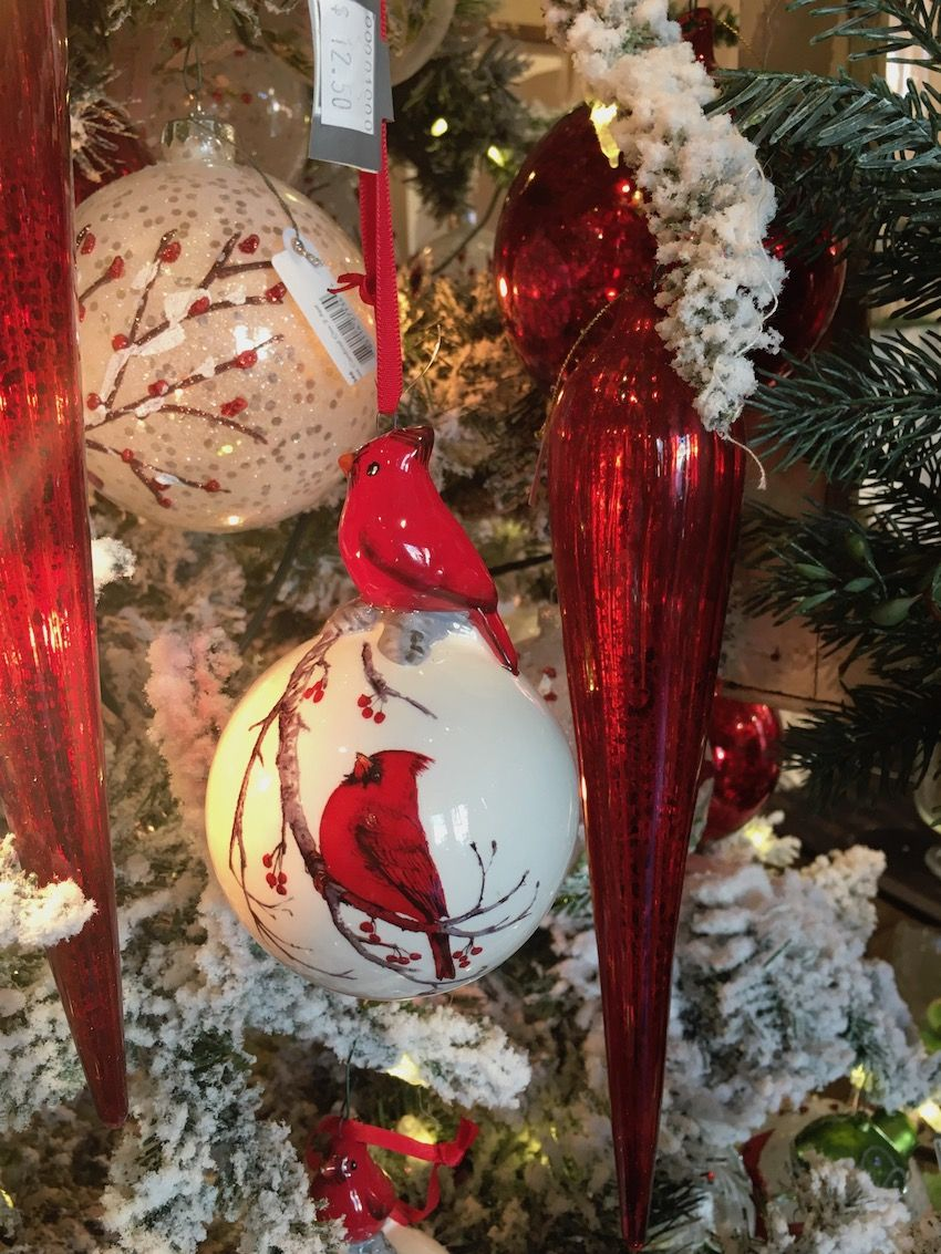 Red cardinals and berry sprigs adorn the ceramic ball ornaments.